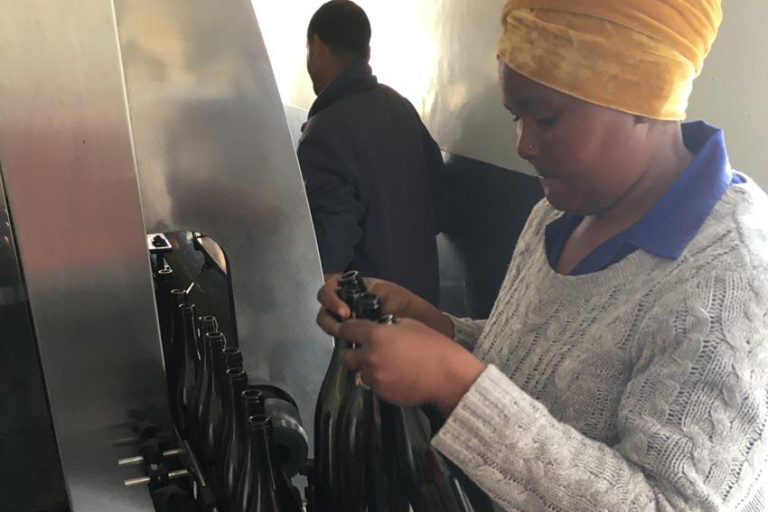 Eine Frau füllt Wein ab.