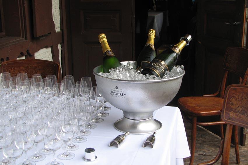 Champagnerschale mit drei Flascehn Champagner und vielen Gläsern.
