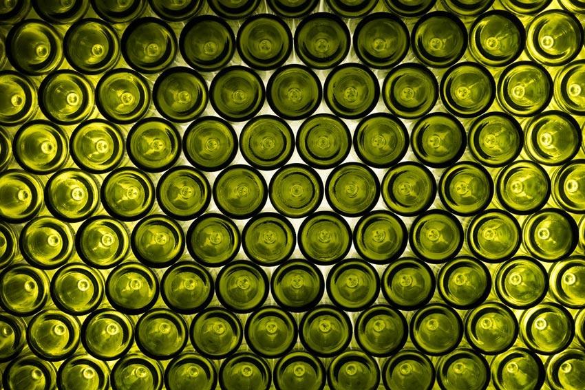 Viele grüne Weinflaschen aneinandergereiht.